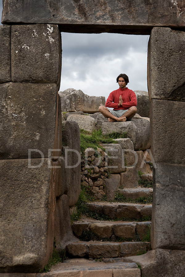 A young man meditates in ancient monolithic Inca fortress ruins of Sacsayhuaman outside Cuzco, Peru.