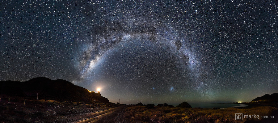 This image was shot in one of my favourite 'dark sky' locations at Cape Palliser on the bottom of the North Island of New Zealand. It is a panorama made up of 28 individual shots, giving an overall image size of 275 megapixels. The photo shows the Milky Way high in the sky stretching from east to west. The Large and Small Magellanic Clouds can be seen below the arch of the Milky Way. These two objects are irregular dwalf galaxies and are only visible from the southern hemisphere. The light below the Milky Way to the left is the Cape Palliser Lighthouse, and the small glow on the horizon to the right is the Queen Mary 2 Cruise Ship en-route for Wellington, New Zealand.