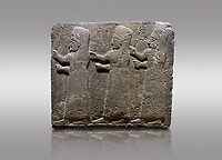 Picture & image of Hittite monumental relief sculpted orthostat stone panel of a Procession Basalt, Kargamis, Gaziantepe, 900 - 700 B.C. Anatolian Civilisations Museum, Ankara, Turkey.<br /> <br /> It is a depiction of three marching female figures in long dress with a high headdress at their head. These women are considered to be the nuns of the Goddess Kubaba. The figures in the front and behind have a bunch of spicy in their right hand while the figure in the middle has an empty right hand. Figures carry objects similar to a sceptre in their left hand. <br /> <br /> Against a gray background.