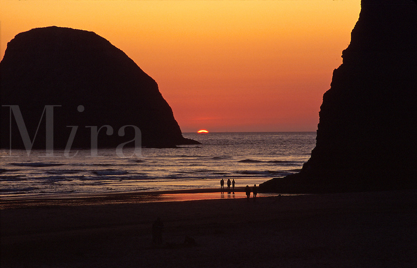 Copper and amber glow of sunset behind Three Arch Rocks with beachcombers in silhouette. scenic, seascape, Pacific ocean. Oceanside Oregon, Oregon Coast.