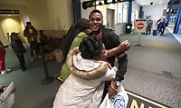 NWA Democrat-Gazette/J.T. WAMPLER John Feruzi gets hugs from his aunt Nyasa Safi and cousin Josephina Richard Tuesday March 20, 2018 at the Northwest Arkansas Regional Airport in Highfill. Feruzi spent years in a refugee camp in Malawi after fleeing his native Republic of the Congo.