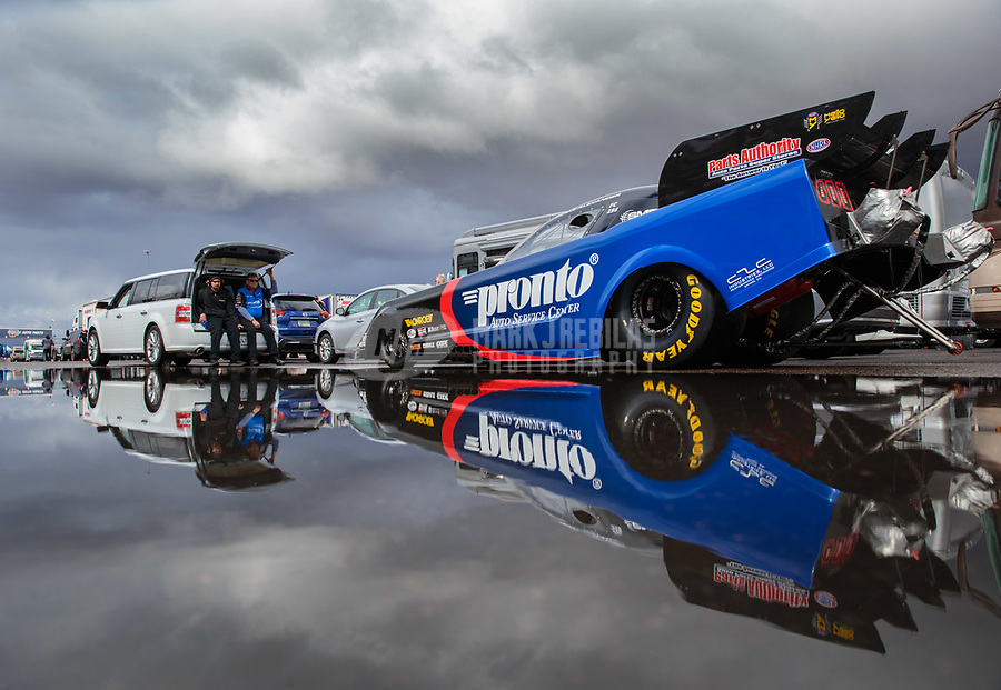 Feb 22, 2019; Chandler, AZ, USA; The car of NHRA funny car driver Blake Alexander reflects in a rain puddle as the car is towed to the staging lanes during qualifying for the Arizona Nationals at Wild Horse Pass Motorsports Park. Mandatory Credit: Mark J. Rebilas-USA TODAY Sports