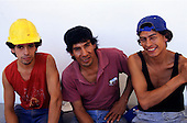Buenos Aires, Argentina. Three construction workers, one with a yellow hard hat one with a blue baseball cap.