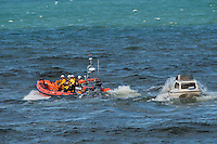 Aberystwyth Wales UK  Wednesday 31 August 2016<br /> Pictured: RNLI crew with the small motor boat that they recovered.<br /> Re: Re: A man tried to save his friend who died after falling out of a speedboat, an inquest has been told.<br /> William George Davies, 63, from Borth, died in August after he was thrown overboard during a fishing trip off Aberystwyth.<br /> A second man, Alan Jones, was also thrown overboard but survived.<br /> The inquest at Aberystwyth Justice Centre was told the cause of death was drowning and coroner Peter Brunton recorded a conclusion of misadventure.<br /> Mr Brunton said he had &quot;concerns&quot; over the fact the two men were not wearing life jackets, the sea had been &quot;choppy&quot; and Mr Jones had taken off the kill cord which would automatically stop the engine if he were thrown overboard.<br /> The inquest heard the men had set out at about 7.30am on 31 August to go fishing, but headed to Aberystwyth harbour a short time later when Mr Davies started to feel unwell - which his friend put down to sea sickness.