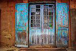 Weathered blue shutters, glass-paned door and red mud brick home front in Ambositra, in the central highlands of Madagascar.