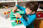 Education preschool 3-4 year olds boy building by stacking number pegboards