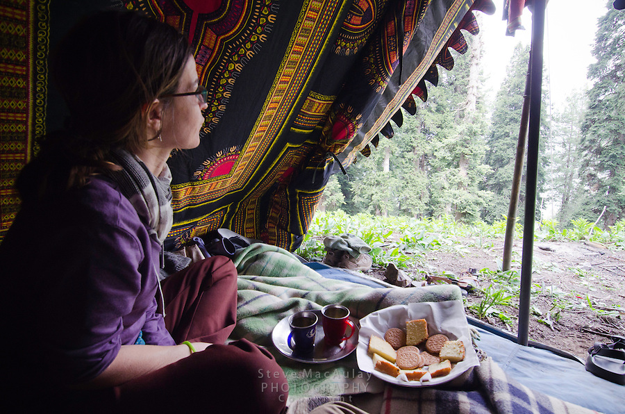 Female tourist enjoying tea and sweets at the door of a Kashmiri trekking tent, Western Himalayan Mountains, Kashmir, India..