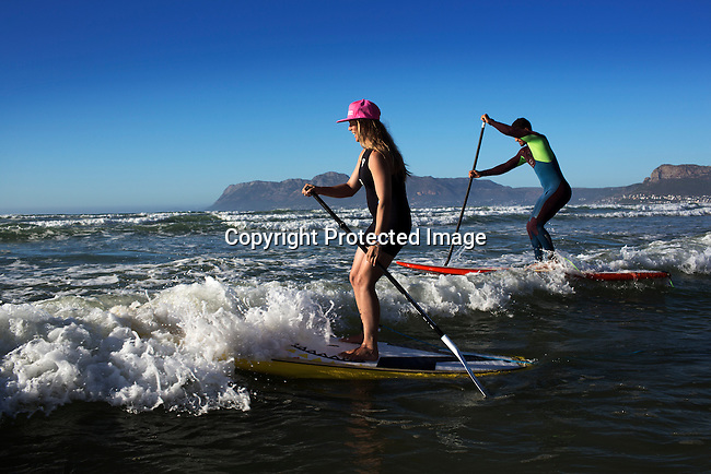 A couple does stand up paddle boarding in Muizenberg beach outside Cape Town, South Africa. Cape Town has become one of the worlds must see cities, with its natural beauty, beautiful weather and outdoor activities. (Photo by: Per-Anders Pettersson)