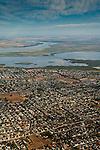 Aerial over suburban tract housing neighborhood communities and the Sacramento - San Joaquin River Delta, Antioch, California