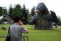 """July 18, 2014, Tokyo, Japan - A man takes pictures of the 6.6 meter model of the new Godzilla at Tokyo Midtown on July 18, 2014, Tokyo. The statue is a 1/7 scale reproduction of the 180 meters tall Hollywood film version of """"GODZILLA"""".  Godzilla and its footprints will be displayed from July 18 to August 31 during which time it will perform a special show using mist, light and sound effects every 30 minutes between 19:00 to 21:00. (Photo by Rodrigo Reyes Marin/AFLO)"""
