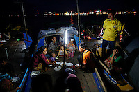 Ethnic Cham Muslim people eat their Iftar (breaking fast) meals on banks of Tonle Sap river in Phnom Penh July 29, 2013. About 100 ethnic Cham families, made up of nomads and fishermen without houses or land who arrived at the Cambodian capital in search of better lives, live on their small boats on a peninsula where the Mekong and Tonle Sap rivers meet, just opposite the city's centre. The community has been forced to move several times from their locations in Phnom Penh as the land becomes more valuable. They fear that their current home, just behind a new luxurious hotel under construction at the Chroy Changva district is only temporary and that they would have to move again soon. Picture taken July 27, 2013.   REUTERS/Damir Sagolj (CAMBODIA)