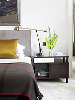 A glass topped table with an angle-poise lamp is one of a pair of bedside tables in this contemporary bedroom