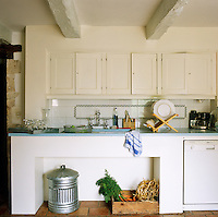A blue-painted contemporary work surface echoes the rustic style of this country kitchen