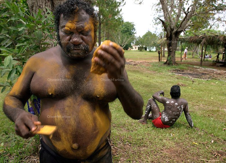 An aboriginal man paints his body for a cleansing ceremony on Tiwi Islands.  Body paint seems to be primarily decorative instead of storytelling.  Culture is more intact because the island is removed from modern western culture.  <br /> <br /> A cleansing ceremony is the final ceremony in the death of a family member.  A year or so after the funeral the family gets together and paints pukamani poles and places them around the grave.  Some communities won't say the name of the deceased or go back into the home until there is a big cleansing rain.  But rituals vary from community to community. <br /> Relatives of this family brought pukamani poles from Snake Bay on the other side of the island.  They continued with this ceremony even though there was an impending cyclone.  Even though the ceremony is supposed to be a year or two after the death--often it is held just before Xmas at the beginning of the wet because everyone gets their Xmas club money around that time and there is an exchange of money at the end of the ceremony. The family also has to pay the dancers and totem carvers.  The family elder for this ceremony is Justin Puruntatameri. <br /> Tiwi has two islands--Bathurst and Melville.  This ceremony is in the town of Garden Point on Melville Island.  Melville Island is 2nd largest island in Australia... Tasmania is largest.