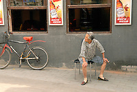 A women takes a seat under a Budweiser sign near one of Beijing's oldest neighborhoods. Beijing's hutongs are a disappearing cultural treasure and a remnant of the city's 14th-century design..