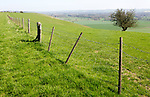 Fence running along top of chalk scarp slope looking south east over Vale of Pewsey, near Knap Hill, Wiltshire, England, Uk
