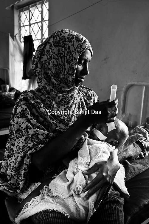 An young woman gives oral rehydration to her infant malnutrioned child at the stabilization ward of the GIZ Main Hospital in the Dadaab refugee camp in northeastern Kenya. Photo: Sanjit Das/Panos