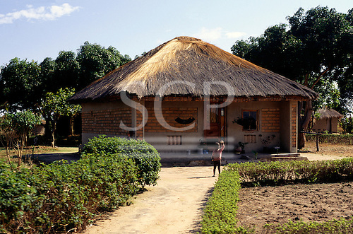 Lusaka, Zambia, Africa. A boy waves from the front of his neat house and garden.