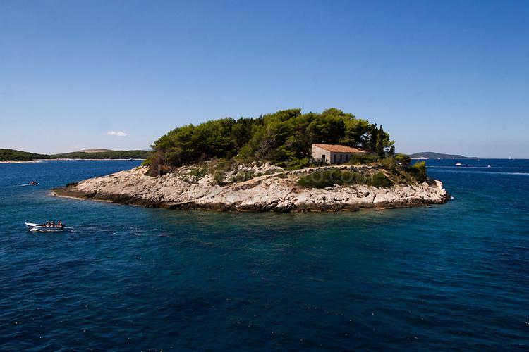 The island of Gale?nik, in the Paklinski archipelago, near Hvar, Croatia, with a boat passing by