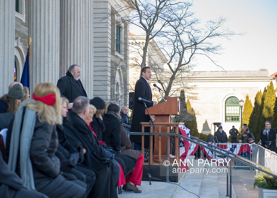 Mineola, New York, USA. January 1, 2018. New York Governor ANDREW CUOMO is speaking at poidum during historic swearing-In of Laura Curran as Nassau County Executive, the first female County Executive. Cuomo administered the Oath of Office to Curran. Nassau County Legislators are seated left of Cuomo. Temperature was a freezing 14 ℉ Fahrenheit / -10 ℃  Celsius for the outdoor ceremony held in front of Theodore Roosevelt Executive & Legislative Building. Standing behind Cuomo is Mayor FRANCIS MURRAY of Rockville Centre.
