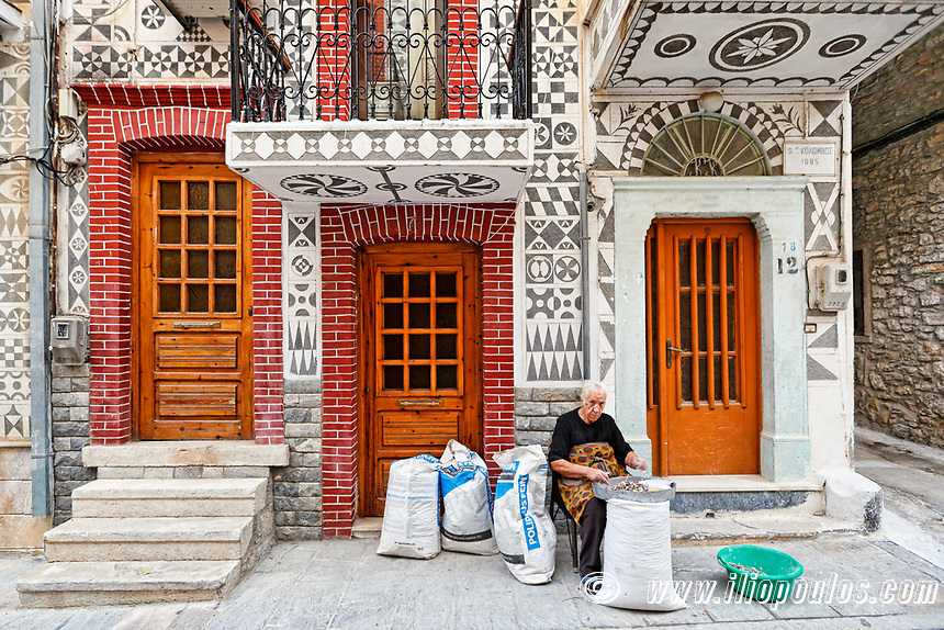 Local woman work outside a traditional house decorated with the famous geometric scratch patterns in the medieval mastic village of Pyrgi on the island of Chios, Greece