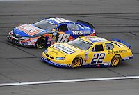 Oct. 3, 2009; Kansas City, KS, USA; NASCAR Nationwide Series driver Parker Kligerman (22) races alongside Kyle Busch (18) during the Kansas Lottery 300 at Kansas Speedway. Mandatory Credit: Mark J. Rebilas-