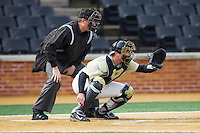 Wake Forest Demon Deacons catcher Garrett Kelly (28) sets a target as home plate umpire Jamie Roebuck looks on during the game against the Marshall Thundering Herd at Wake Forest Baseball Park on February 17, 2014 in Winston-Salem, North Carolina.  The Demon Deacons defeated the Thundering Herd 4-3.  (Brian Westerholt/Four Seam Images)