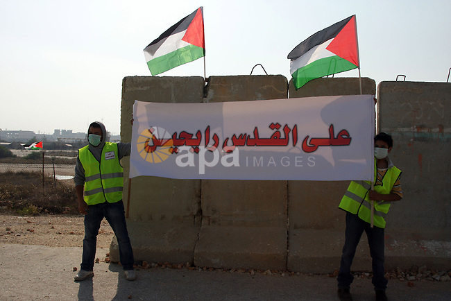 """Local and international peace activists during a protest in the Qalandia refugee camp, near the West Bank city of Ramallah, on November 9, 2009 to mark the 20th anniversary of the fall of the Berlin Wall in Germany. Palestinians are using the anniversary of the end of the Berlin wall to press their campaign against Israel's """"wall"""", mostly a razor-wire fence interspersed with concrete barricades which Israel began building around the West Bank in 2002. The Jewish state has come under international censure for the barrier's de facto annexation of occupied West Bank land.. Photo by Issam Rimawi"""
