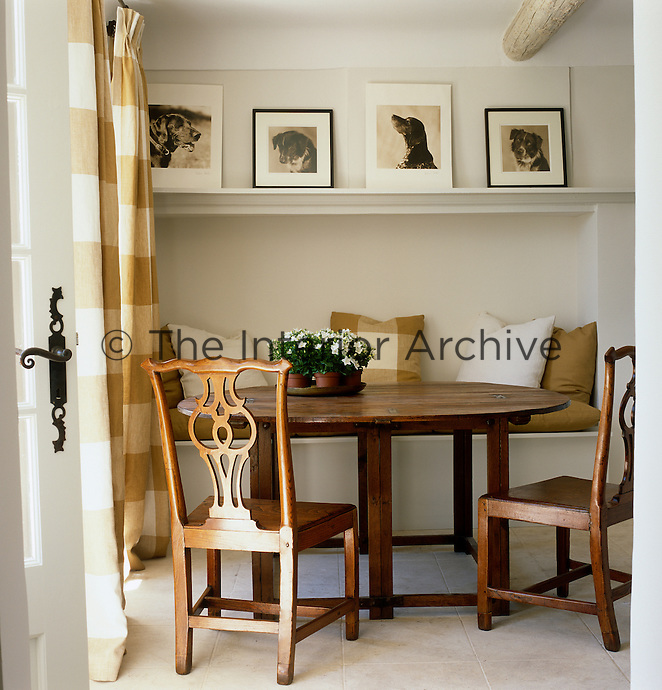 The dining area in the kitchen has been created with a recessed banquette and Chippendale chairs surrounding a wooden table