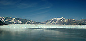 Hubbard Glacier is the largest tidewater glacier on the North American continent. It is 25 percent larger than the state of Rhode Island.  It has been thickening and advancing toward the Gulf of Alaska since it was first mapped by the International Boundary Commission in 1895. In contrast, most glaciers have thinned and retreated during  the last century.  This atypical behavior is an important example of the calving glacier cycle in which glacier advance and retreat is controlled more by the mechanics of terminus calving than by climate fluctuations. It begins its 76 mile journey to the sea on the slopes of Mount Logan, the tallest mountain in Canada and part of the largest non-polar icefield in the world. At the point where it enters Disenchantment Bay, at the head of Yakutat Bay, Alaska, it is 6 miles wide. Blue ice at the face of a glacier means that it is actively calving.