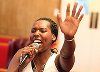 Immacule Nyirabeza raises her hand in worship as she sings during Sunday service at The Africa Lighthouse Baptist Temple near Stony Point in Albemarle County, VA. The small 10 family congregation is made up of African refugees and immigrants who's service is spoken in Swahili and translated into English. They've just signed a rent-own lease for a small church after meeting for three years at a local school. Photo/The Daily Progress/Andrew Shurtleff