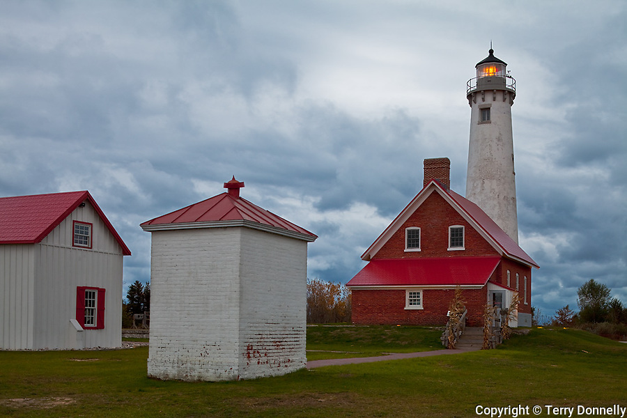 Iosco County, Michigan<br /> Tawas Point Lighthouse (1876) illuminated at dawn beneath low storm clouds, Tawas Point State Park, Lake Huron