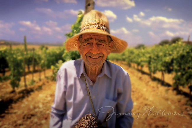 An elderly Italian farmer smiles while standing on his farmland