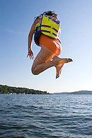 A girl jumping into a lake.