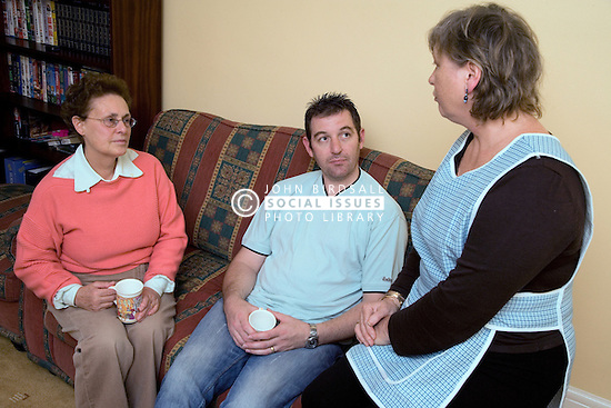Carer talking older woman and her son at home,