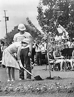 Queen Elizabeth wields a silver-plated shovel as she plants a silver maple tree in Ganaraska Conservation area at Cobourg today in commemoration of Conservation Week. Over 5;000 men; women and children crowded into park to watch the tree-planting ceremony and see the Queen unveil a cairn; during her brief visit.<br /> <br /> Griffin, Doug<br /> Picture, 1973,