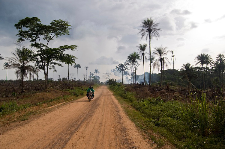 A motorcyle passes fields being burnt for cultivation, Kailahun District. Sierra Leone. Photo taken April 30, 2010.