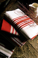 A pile of red and white striped cotton napkins on the rustic table