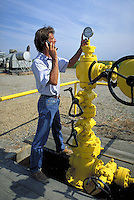 Technician using cellular flip phone while checking valves. Agriculture, technology, evaluation, technician, industrial equipment, work, communication. technician next to valves. Colusa CA USA industrial.