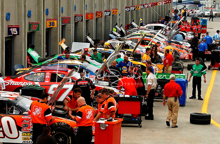 Crew members work in a crowded garage area to assemble and tune their cars prior to qualifications for the Winston at Lowe?s Motor Speedway.