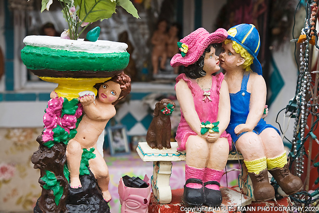 "A pair of figurines seem to represent sweetheats and owners  C. L. ""Tunnie"" Sharpe and his wife Helen, to whom Tunnie has dedicated the creation  of his whimsical folk art garden in Santa Fe, New Mexico"
