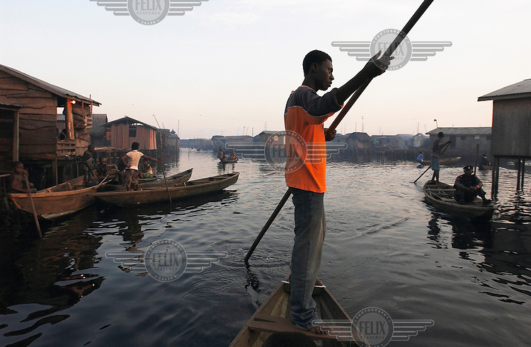 A man pushes his pirogue past houses built on stilts above the water.