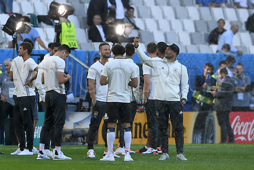 02.07.2016. Bordeaux, France.  Germany's Lukas Podolski (R) takes a selfie next to his team mates Shkodran Mustafi (C) as they inspect the field before the UEFA EURO 2016 quarter final soccer match between Germany and Italy at the Stade de Bordeaux in Bordeaux, France, 02 July 2016.