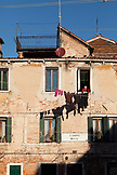ITALY, Venice. An older woman hangs laundry outside her window in the Castello District. Castello is the largest of the six sestieri of Venice.