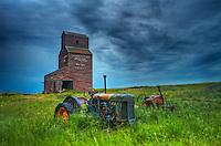 Grain elevators and old tractors in ghost town<br /> Bents<br /> Saskatchewan<br /> Canada