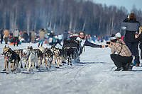 Gus Guenther reaches out for a high-five to race fans on Long Lake during the Iditarod 2014 restart in Willow, Alaska.<br /> <br /> Iditarod Sled Dog Race 2014<br /> PHOTO (c) BY JEFF SCHULTZ/IditarodPhotos.com -- REPRODUCTION PROHIBITED WITHOUT PERMISSION