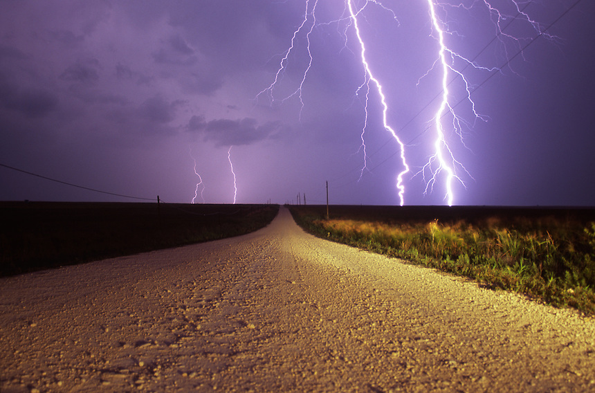 Forked lightning channels stab the earth along a desolate gravel road in western Oklahoma.