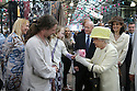 Two year old Stella Sweeney (while in the arms of Dad Connor & Mum Audhild behind) hands with Britain's Queen Elizabeth II a small bunch of flowers as she tours St.Georges Market in Belfast, Tuesday June 24th, 2014. The Queen is on a 3 day tour of Northern Ireland. Photo/Paul McErlane