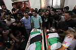 Relatives of two Palestinians, who were killed in an Israeli air strike, mourn over their bodies during their funeral at a mosque in Gaza city on July 15, 2018. Photo by Mahmoud Ajour