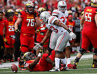Ohio State Buckeyes linebacker Darron Lee (43) helps Maryland Terrapins running back Brandon Ross (45) back up after tackling him in the second quarter of their game at Byrd Stadium in College Park, Maryland on October 4, 2014. (Columbus Dispatch photo by Brooke LaValley)